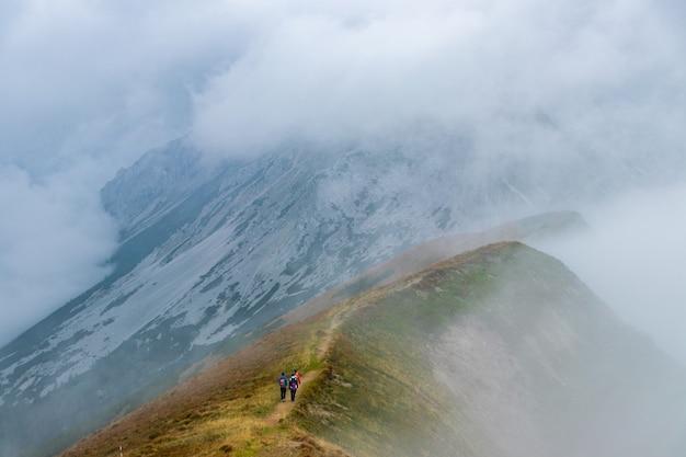 Excursionistas subiendo una montaña alta.