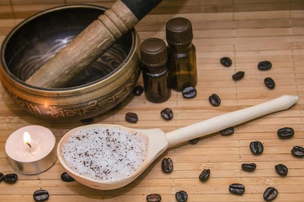 Exfoliante de café, granos de café, cuenco, aceite aromático, estera de paja sobre paja
