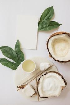 Exfoliante corporal natural hecho a mano con coco y tarjeta en blanco sobre fondo blanco