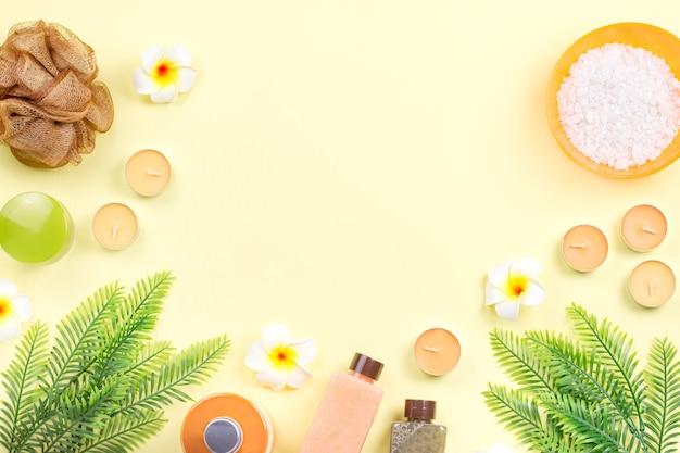 Exfoliante corporal, sal de baño, loción hidratante, velas y hojas sobre amarillo