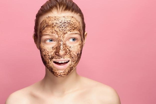 Exfoliante de piel facial. retrato del modelo femenino sonriente atractivo que aplica la máscara natural del café, exfoliante facial en piel facial. primer de la mujer feliz hermosa con la cara cubierta con el producto de belleza.