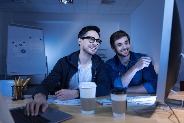 Éxito absoluto. hackers genios encantados y alegres sentados frente a la computadora y robando dinero de cuentas bancarias mientras están felices por su éxito