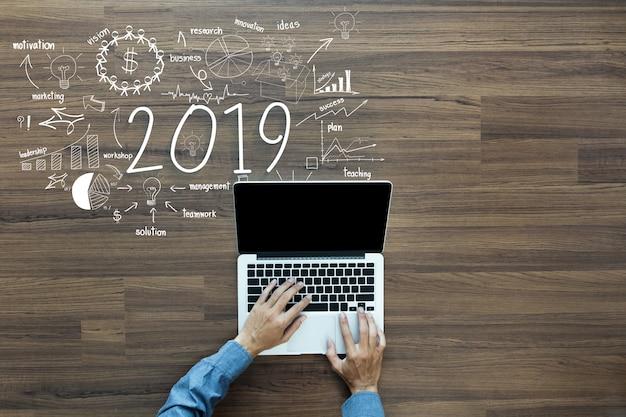 Éxito empresarial de año nuevo de 2019 con un empresario que trabaja en una computadora portátil