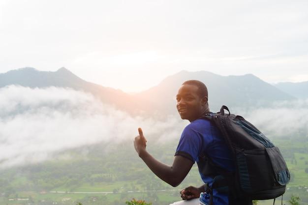 Éxito escaladores africanos que buscan en la cima de la colina cubierta de niebla y lluvia.