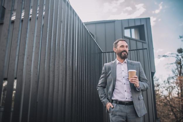 Éxito. exitoso hombre de negocios sonriente en traje gris con café cerca de la oficina en la calle de buen humor