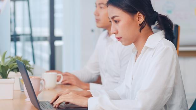 Éxito hermoso ejecutivo asia joven empresaria elegante ropa casual viendo tutorial sobre ideas creativas en la computadora portátil durante el proceso de trabajo en el lugar de trabajo de la oficina moderna.