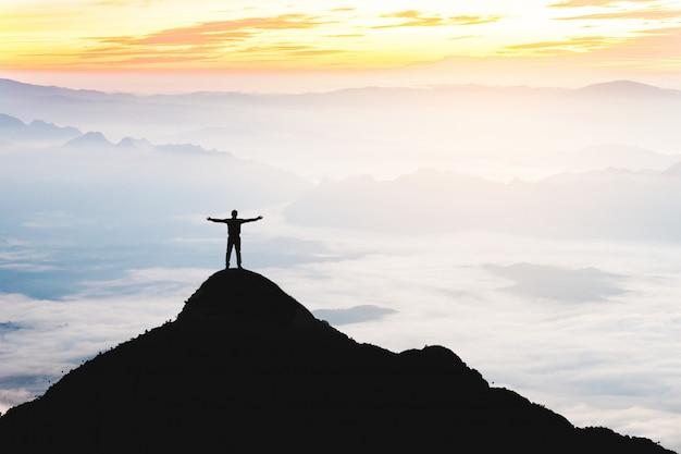 El éxito del hombre de negocios que levanta los brazos se coloca encima de la colina