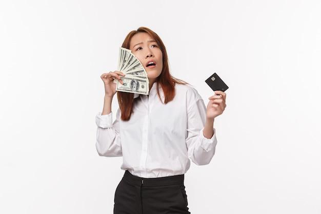Éxito, mujeres y concepto de carrera. satisfecho, satisfecha y jactanciosa, joven asiática que disfruta de ser rica, con tarjeta de crédito y cepillarse las mejillas con dólares, tiene mucho dinero