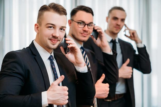Éxito en el negocio. hombres en trajes gesticulando los pulgares para arriba
