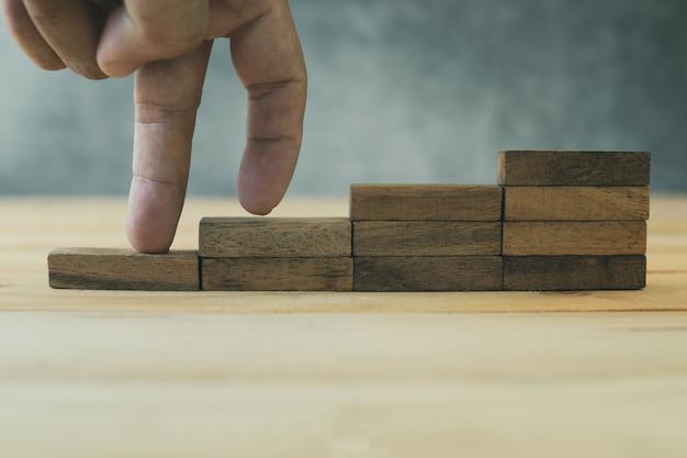 El éxito y el negocio que crecen concepto, dedo intensifican en madera