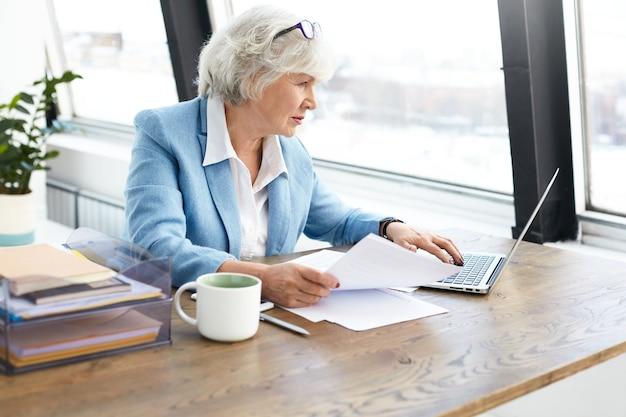 Exitosa abogada anciana con experiencia con un bonito traje y gafas en la cabeza usando una computadora portátil en su lugar de trabajo, mirando la pantalla con una expresión facial concentrada y enfocada