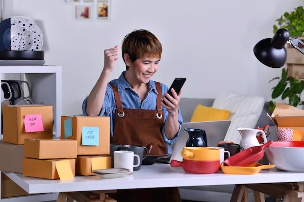 Exitosa empresaria asiática madura, dueña de un negocio con el brazo hacia arriba feliz mientras mira su pedido en línea desde el teléfono inteligente. trabajo de negocios de venta en línea en concepto de hogar