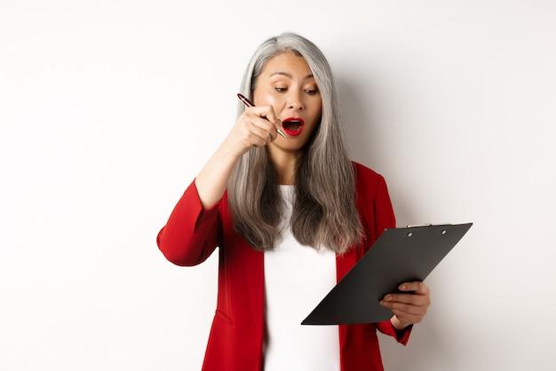 Exitosa empresaria asiática tomando notas en el portapapeles, trabajando en el informe y mirando emocionada, de pie sobre fondo blanco.