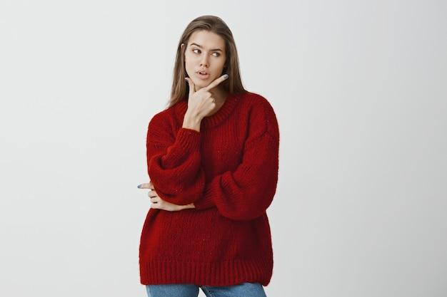Exitosa empresaria decidiendo cómo escapar de la situación incómoda. foto de una mujer europea hermosa y seria con suéter rojo suelto, sosteniendo la mano por encima de la barbilla y pensando, siendo intenso sobre la pared gris