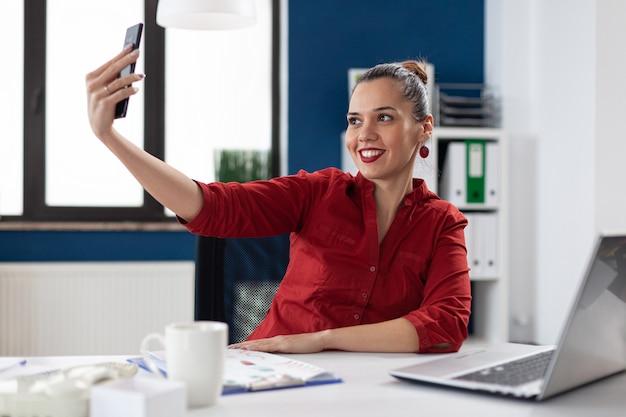 Exitosa empresaria divirtiéndose en wwork tomando selfies