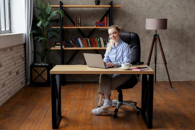 Exitosa empresaria joven sonriente usando laptop y computadora en la oficina. foto de alta calidad