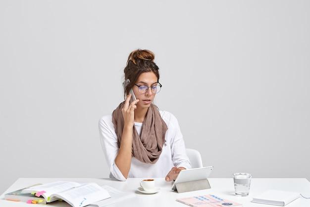 Exitosa empresaria próspera ocupada comprueba las notas en el panel táctil mientras llama a través de un teléfono inteligente