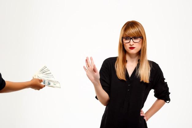 Exitosa empresaria rechazando dinero sobre pared blanca