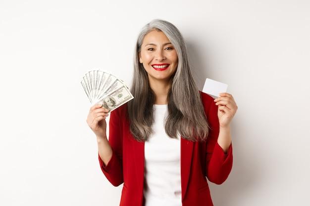 Exitosa empresaria senior asiática mostrando dinero en dólares y tarjeta de plástico, sonriendo feliz a la cámara, vistiendo chaqueta roja y maquillaje