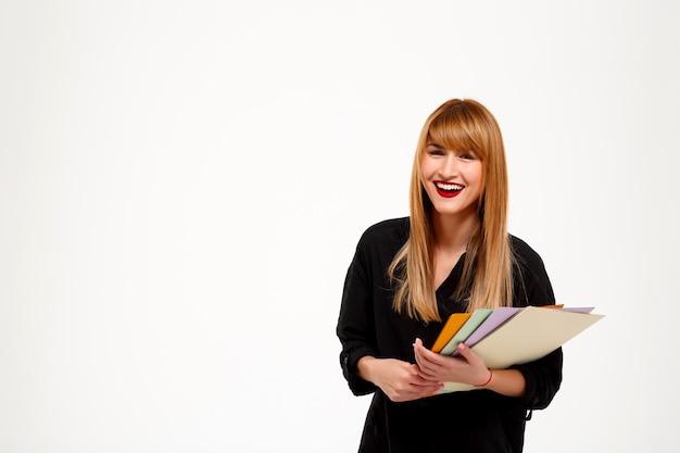 Exitosa empresaria sonriente sosteniendo carpetas sobre pared blanca copie el espacio.