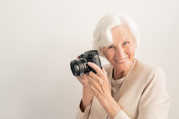 Exitosa fotógrafa senior con cámara mirándote con una gran sonrisa sobre la pared blanca en aislamiento