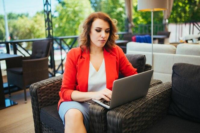 Exitosa mujer de negocios usando la computadora portátil mientras está sentado en el café salón.