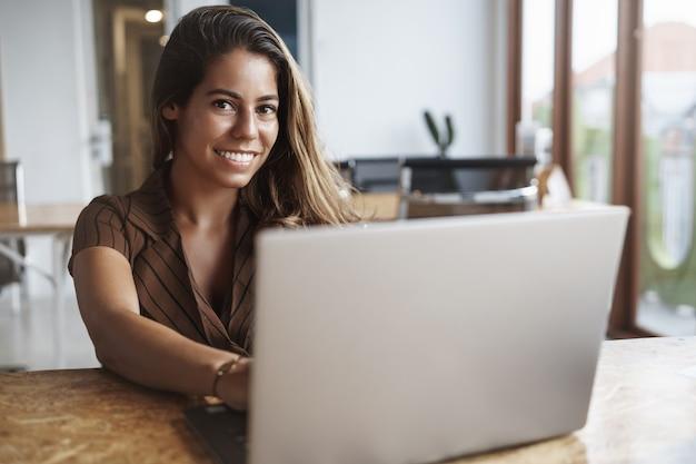 Y exitosa mujer hispana sonriendo con laptop en cafe