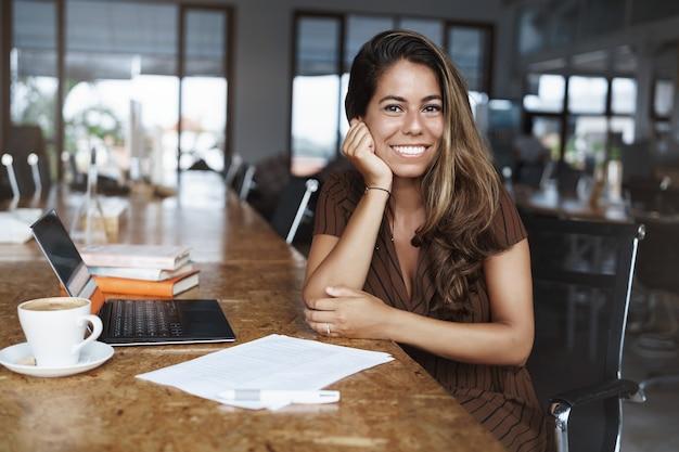 Y exitosa mujer hispana sonriendo trabajando en cafe
