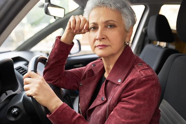 Exitosa mujer de mediana edad moderna en ropa elegante habiendo trastornado facial dentro de su coche