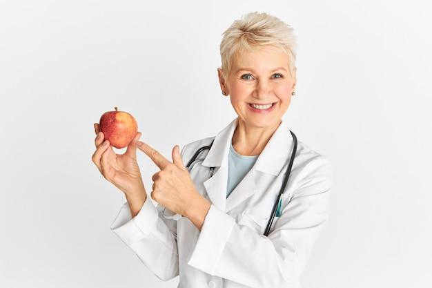 Exitosa mujer de mediana edad con uniforme médico sonriendo a la cámara y apuntando con el dedo índice a la manzana roja madura que es buena para la salud intestinal y promueve la pérdida de peso. salud y dieta