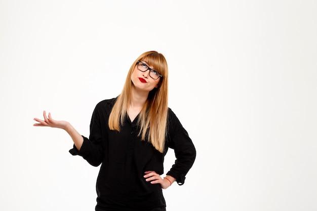 Exitosa mujer de negocios gesticulando o pensando sobre la pared blanca copia espacio