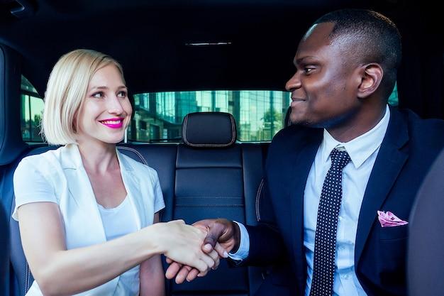 Exitosa mujer de negocios rubia empresario empresario con maquillaje en vestido blanco con un apuesto empresario afroamericano jefe hombre en apretón de manos de chaqueta de traje elegante negro trabajando en coche buen trato
