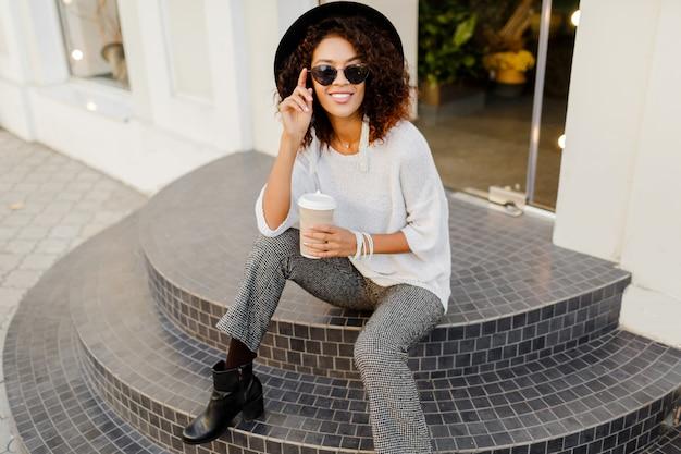 Exitosa mujer negra, blogger o gerente de la tienda hablando por teléfono móvil durante el descanso para tomar café. sentado en las escaleras y sosteniendo la taza de papel de bebida caliente.