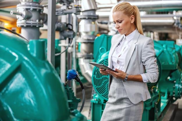 Exitosa mujer trabajadora sonriente gerente en traje de pie en la planta de calefacción con tableta en las manos y comprobando la turbina