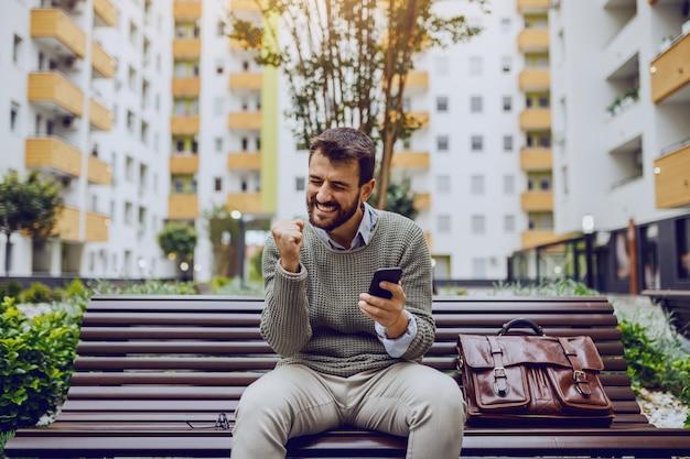 Exitoso apuesto hombre de negocios caucásico de moda sentado en el banco en el parque, leyendo el mensaje en el teléfono inteligente y regocijándose por el logro. junto a él hay un bolso de cuero.