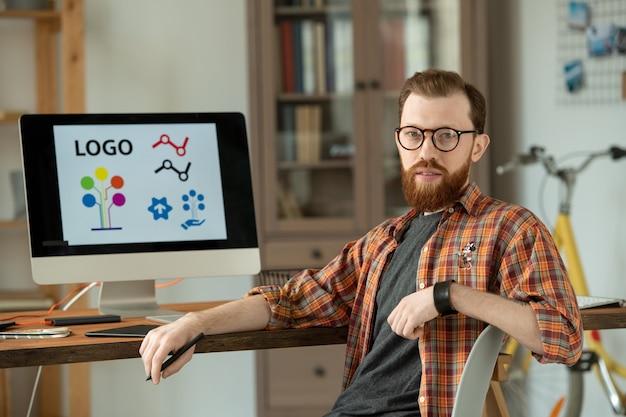 Exitoso diseñador masculino sentado en una silla junto a la mesa frente a la cámara y mirándote sobre el fondo del monitor de la computadora con el logo en