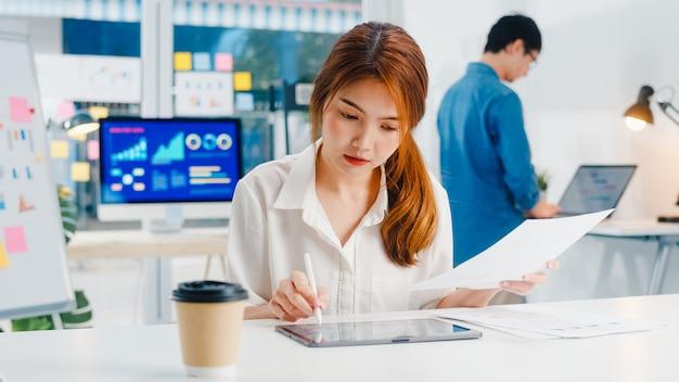 Exitoso ejecutivo de asia joven empresaria elegante ropa casual dibujando, escribiendo y usando lápiz con tableta digital pensando en el proceso de trabajo de ideas de búsqueda de inspiración en la oficina en casa moderna.
