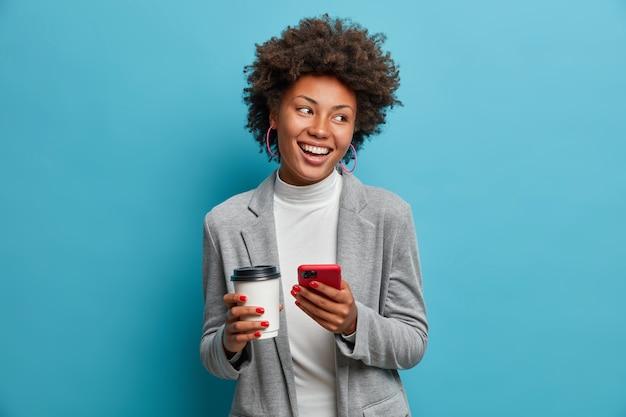 Exitoso empresario afroamericano con ropa formal sostiene el teléfono móvil, pide el almuerzo en línea, bebe café para llevar, revisa el mensaje, hace una nueva cita, mira con una amplia sonrisa brillante a un lado