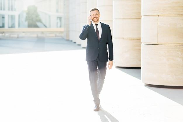 Exitoso empresario masculino en ropa formal, hace una llamada telefónica a su pareja a través del teléfono móvil