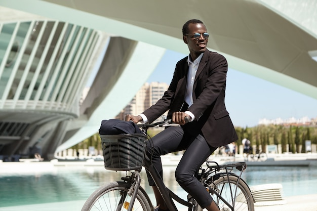 Exitoso gerente afroamericano feliz en traje negro que viaja a la oficina en bicicleta. empleado de piel oscura que se apresura a trabajar en bicicleta. transporte ecológico, estilo de vida urbano y transporte.
