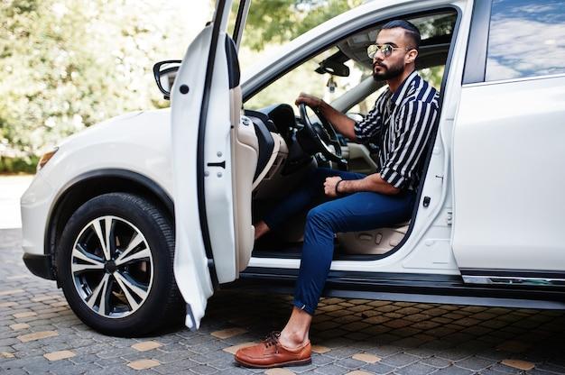 El exitoso hombre árabe con camisa a rayas y gafas de sol posan al volante de su automóvil todoterreno blanco. hombres árabes con estilo en el transporte.