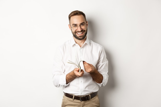 Exitoso hombre de negocios en camisa blanca, contando dinero y sonriendo satisfecho, de pie sobre fondo blanco.