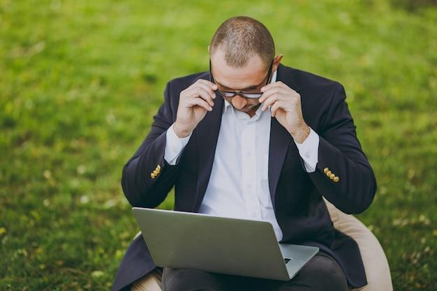 Exitoso hombre de negocios con camisa blanca, traje clásico, gafas correctas. el hombre se sienta en un puf suave, trabaja en un ordenador portátil en el parque de la ciudad en el césped verde al aire libre en la naturaleza. oficina móvil, concepto de negocio.