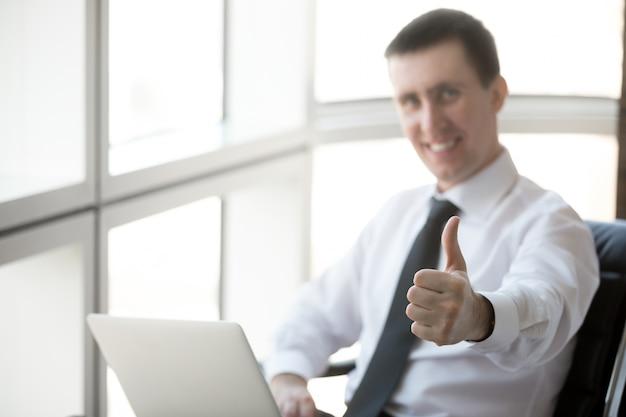 Exitoso hombre de negocios que muestra los pulgares para arriba