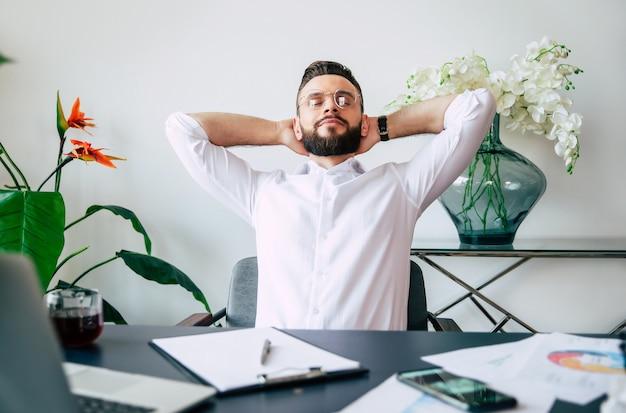 El exitoso hombre de oficina de barba moderna tiene un descanso después de un trabajo duro y bueno en su escritorio de trabajo
