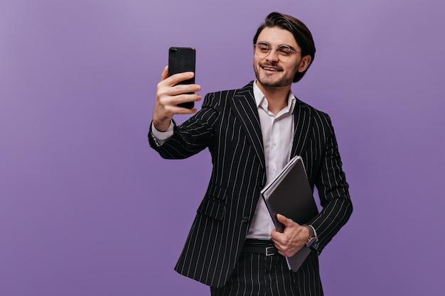 Exitoso joven caballero con camisa blanca, traje negro a rayas y gafas de moda haciendo selfie con carpetas y sonriendo
