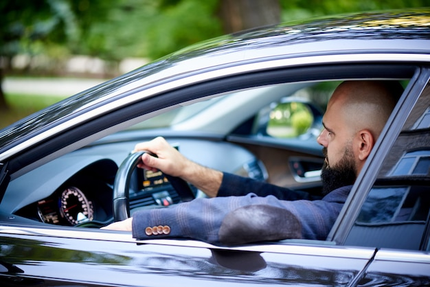 Exitoso joven conduciendo un coche.