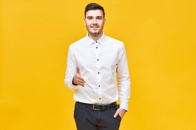 Exitoso joven confiado en camisa blanca formal y pantalón clásico sonriendo y extendiendo la mano para estrechar la suya, haciendo un gesto de bienvenida y saludo, listo para llegar a un acuerdo