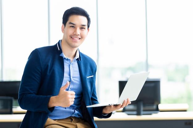 Exitoso joven empresario asiático mostrando los pulgares para arriba