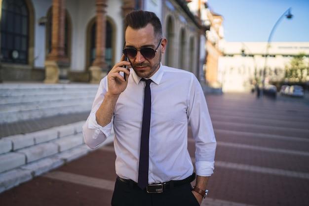 Exitoso joven empresario con un traje formal con gafas de sol hablando por teléfono